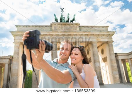 Close-up Of Young Happy Couple Taking Selfie In Front Of Brandenburg Gate In Germany