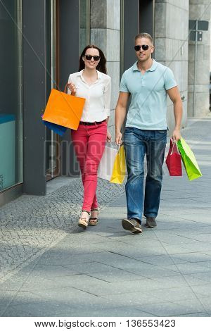 Young Happy Couple Walking On Footpath Holding Multi-colored Shopping Bags