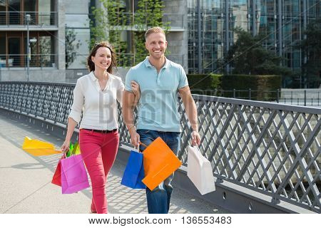 Young Happy Couple Walking On Bridge With Multi-colored Shopping Bags