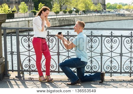 Young Man With Ring Making Proposal To Woman
