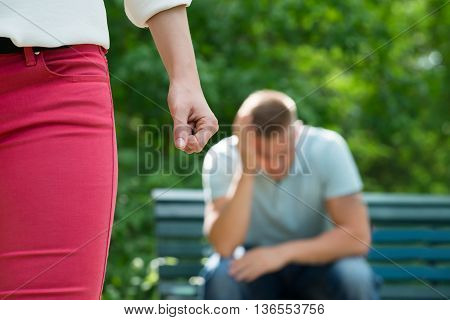 Close-up Of Female's Fist In Front Of Sad Man Sitting On Bench
