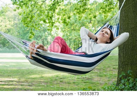 Young Happy Woman Relaxing In Hammock At Garden