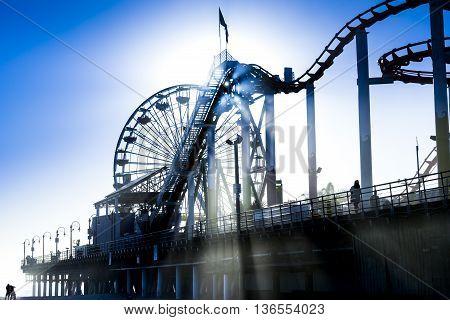 silhouette of ferris wheel and roller coaster on pier in Santa Monica California
