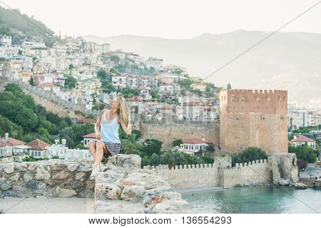 Young blond woman tourist sitting on ancient fortress wall of Alanya castle. Kizil Kule or Red Tower at background. Turkey, Mediterranean region.