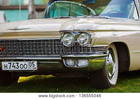 MINSK BELARUS - MAY 07 2016: Close-up photo of beige Cadillac de Ville 1959 model year. Headlight of vintage car. Close-up detail of retro auto. Selective focus.