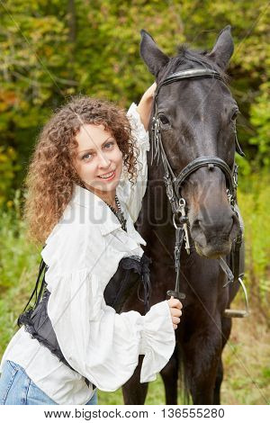 Smiling woman with curly hair stands with bay horse in the park.