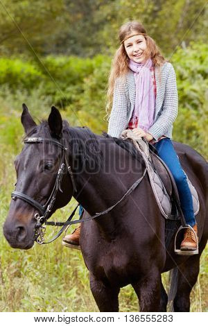Smiling teenage girl sits on chestnut horse in the park.