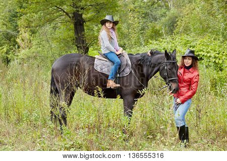 Woman in red jacket holds by the bridle horse on whom her daughter sits. Both in cowboy hats.