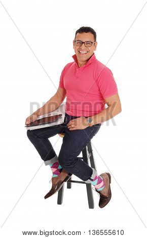 A happy Hispanic man sitting on a chair smiling with the mew's paper and his tablet on his lap isolated for white background.