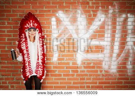 Young woman dressed in costume made of red and white feathers stands her back to the brick wall and holding spray can.