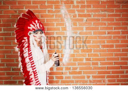 Young woman dressed in costume made of red and white feathers paints on the brick wall with spray.
