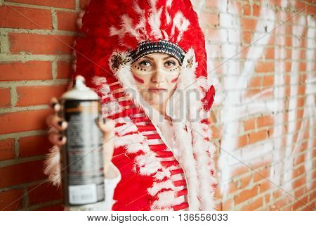 Young woman dressed in costume made of red and white feathers stands her back to the brick wall and holding spray can in outstretched hand.