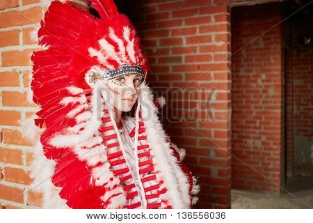 Young woman dressed in costume made of red and white feathers stands leaning her back to the brick wall.