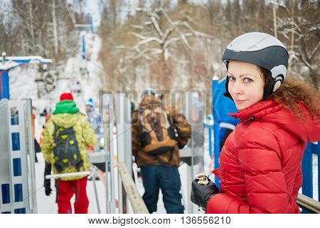 Young woman equipped for skiing near turnstile at ski resort.
