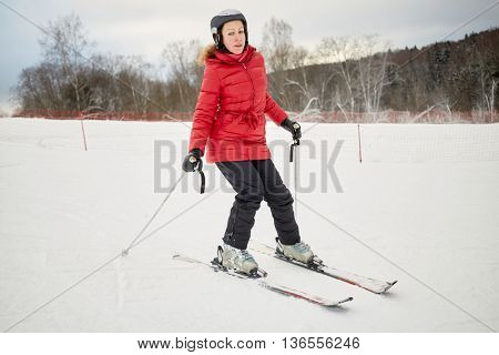Woman skis on slope in winter day at sports complex.