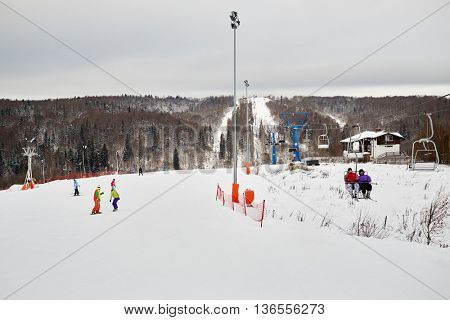 People skiing and snowboarding at winter ski slope.