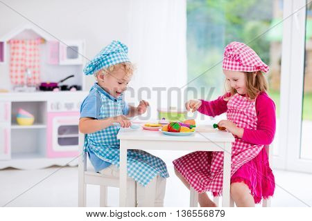 Little girl and boy in chef hat and apron cooking in toy kitchen. Educational toys for young children. Kids play cut wooden vegetables and cook. Toddler kid playing with stove pans and dishes.