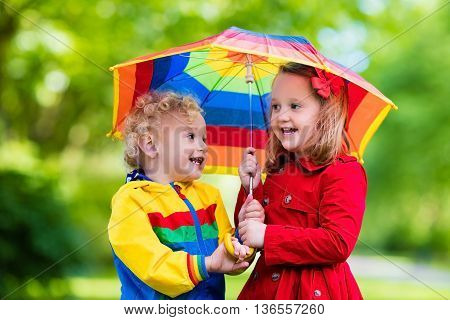 Little boy and girl play in rainy summer park. Children with colorful rainbow umbrella waterproof jacket and coat playing in the rain. Kids walk in autumn shower. Outdoor fun by any weather.