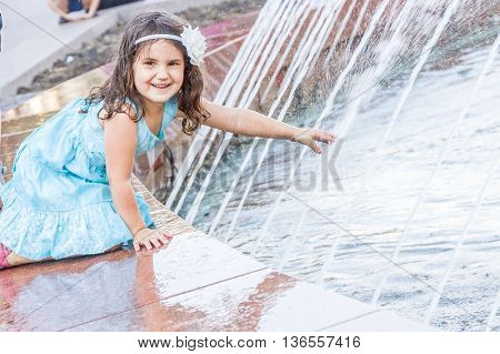 young happy child girl playing with water fountain, outdoor portrait