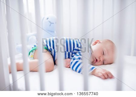 Sleeping baby and his toy in white crib. Nursery interior and bedding for kids. Cute little boy napping in bassinet. Kid taking a nap in white bedroom. Healthy child in bodysuit pajamas.