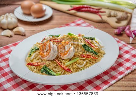Plate of fried vermicelli with shrimps and herbs on the table in restaurant