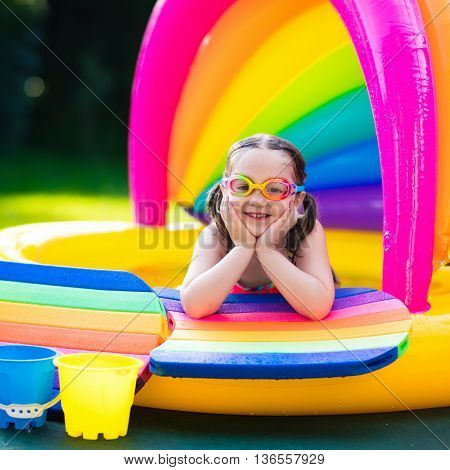 Little girl with goggles playing in inflatable baby pool. Kids swim and splash in colorful garden play center. Children with water toys on hot summer day. Family having fun outdoors in the backyard.