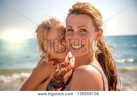 mother holding daughter laughing in camera