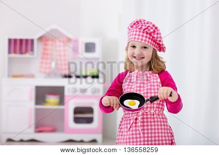 Little girl in chef hat and apron cooking fried eggs in toy kitchen. Wooden toys for young children. Kids play and cook at home or daycare. Toddler kid playing with stove tableware pans and dishes.
