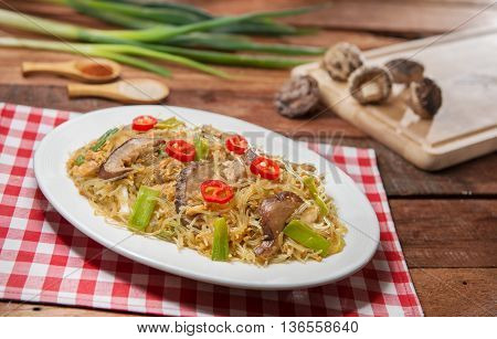 Plate of fried vermicelli with mushroom on the table in restaurant