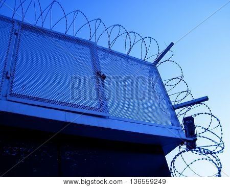 close up shot of security camera and barbed wire fence at night