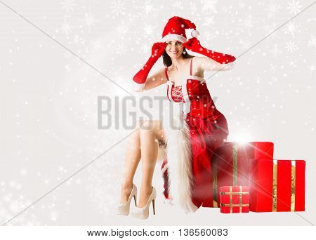 Attractive woman in Santa Clause outfit sitting at the Christmas present box
