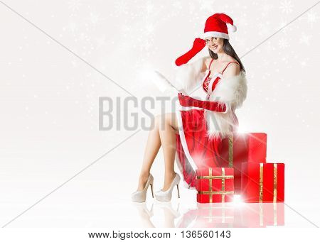 Attractive woman in Santa Clause outfit reading letter to Santa. Christmas background