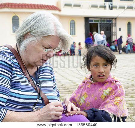 June 2016, Ecuadorian women near Riobamba, Ecuador, sit together while working on a craft and visiting