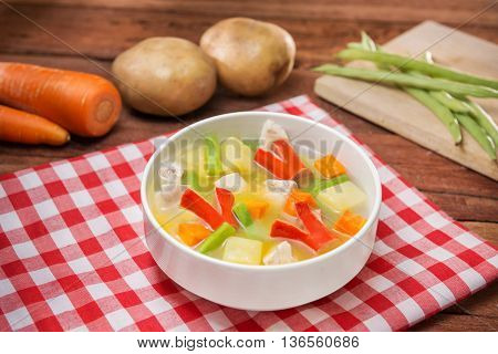 Bowl of vegetables soup with chili cube pork carrot and green pumpkin on the table in restaurant