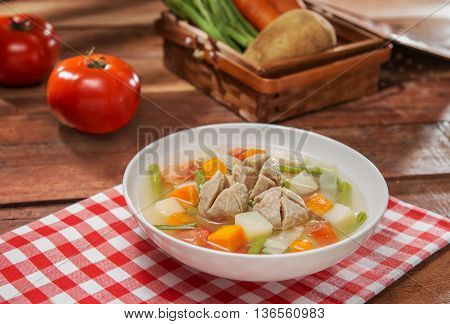 Bowl soup of vegetables and beef balls on the table in restaurant