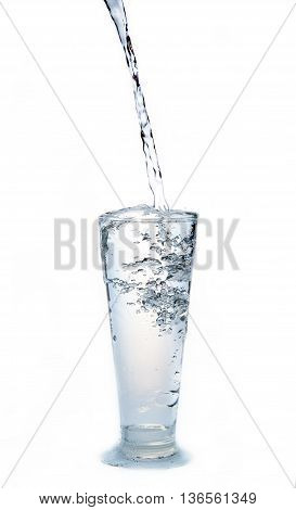 Water flow in to glass on white background