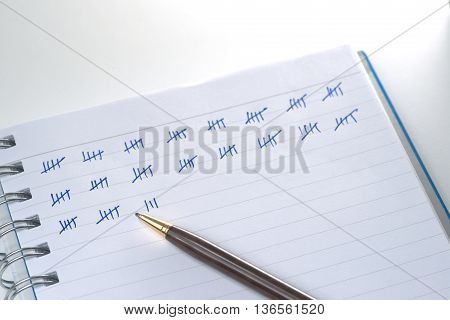 Counting technique by using pen drawing group of bar with 4 vertical and 1 diagonal cross the group on business notebook over white desk with spot ligthing from top right corner