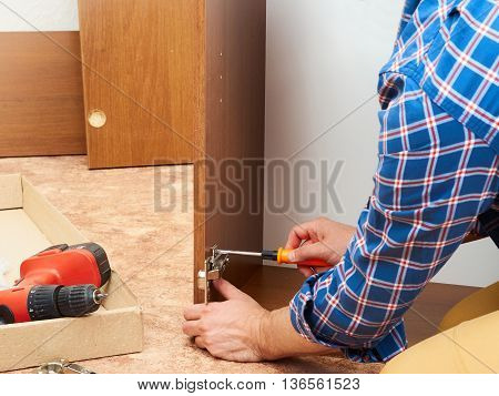 Man in shirt assemble furniture. Domestic work. Craftsman. Carpenter.