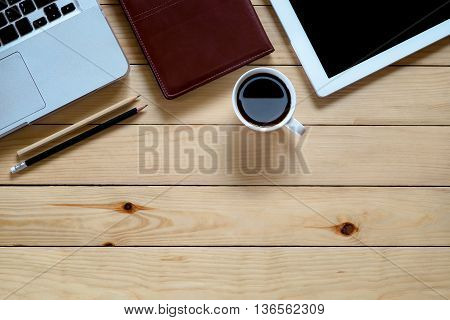 Designer desk with labtop blank screen tablet leather notebook pencils and cup of coffee. Top view with copyspace. Flat lay image.