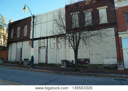 JOLIET, ILLINOIS / UNITED STATES - NOVEMBER 1, 2015: Boarded-up storefronts and abandoned buildings create the impression of a ghost town in downtown Joliet.