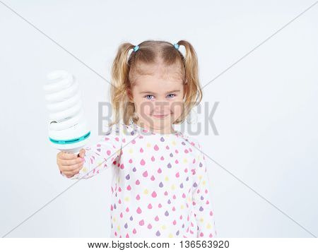 Little Girl Shows A Large Energy-saving Light Bulbs.