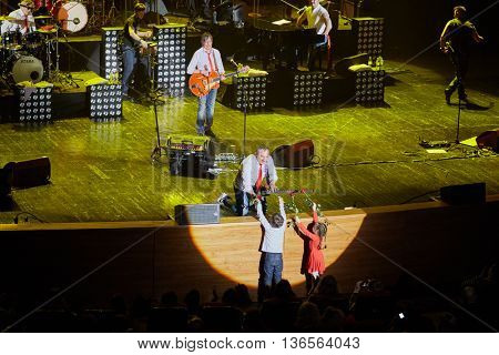 MOSCOW, RUSSIA - APR 24, 2015: N.Fomenko takes flowes from boy and girl on stage in Crocus city hall. Secret band presents concert program On any side of Earth.