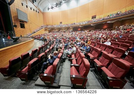 MOSCOW, RUSSIA - APR 24, 2015: People in chairs in central passage, hall and balcony in Crocus city hall at band Secret show. Rock and roll band Secret founded in 1982 in Leningrad.