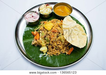 Indian vegetarian food with fried rice on banana leaf tray
