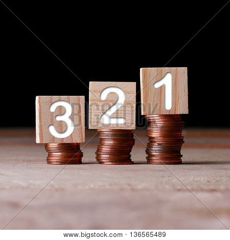 321 number with wooden block on stacked coins