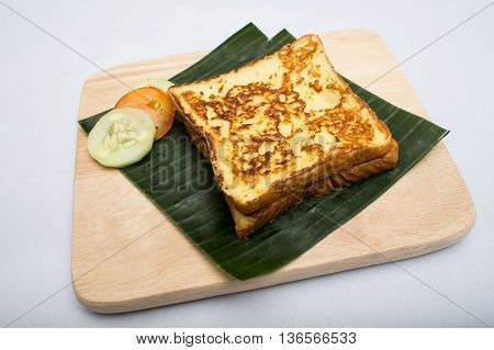 Indian tray meal with roasted sandwich and cucumber tomato on banana leaf