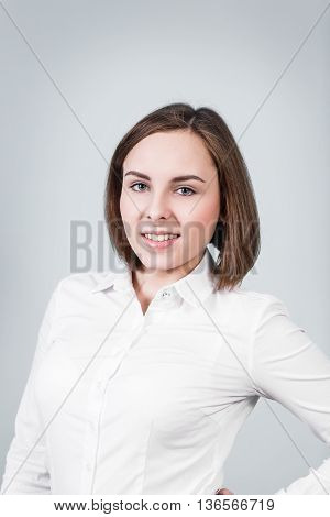 Young beautiful woman with cute smile on the gray background