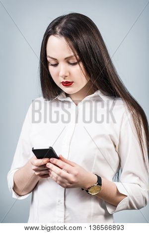 Young woman using a mobile phone over gray background