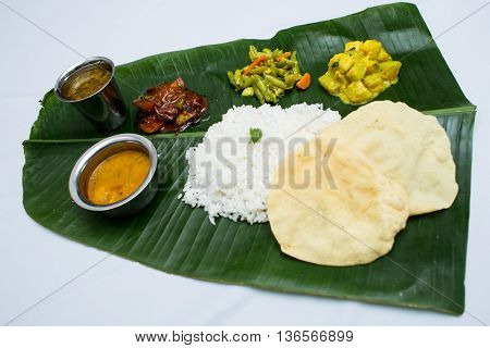 Indian vegetarian food with plain rice on banana leaf tray