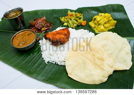 Indian meal with fish and plain rice on banana leaf tray